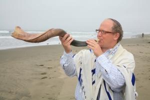 Rabbi Mark Melamuth from B'nai Emunah blowing the shofar by the beach