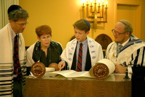 Joshua Edwards reading from the Torah with Cantor Linda Semi and Rabbi Mark Melamut.